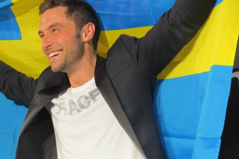 A man holding a Swedish flag in celebration of Eurovision Song Contest