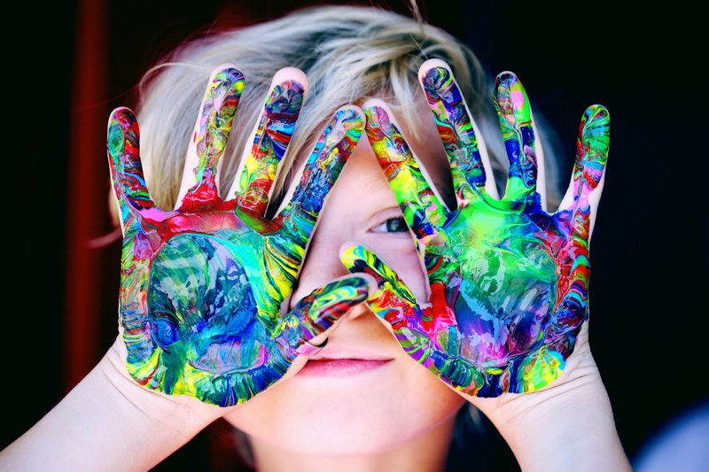 A photo of a child with their hands in front of their face. Their hands are covered in paint in a rainbow of different colours