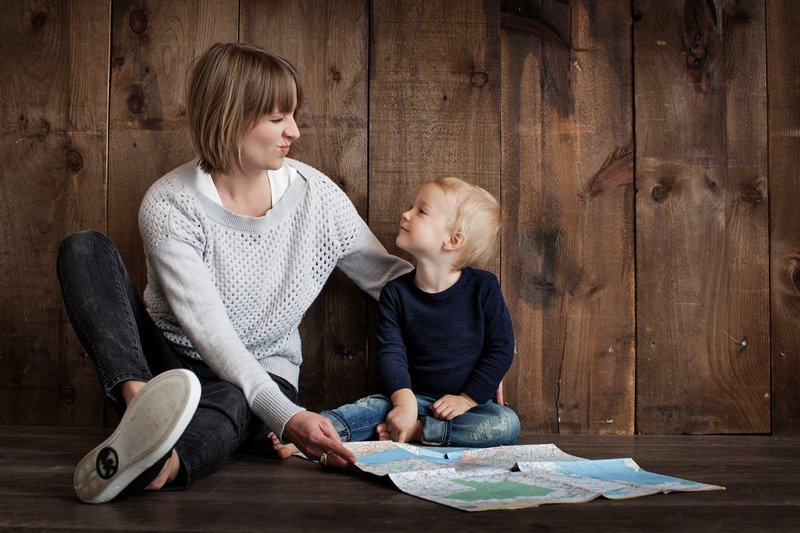 Photo of a mother and child sharing a moment while pouring over a map