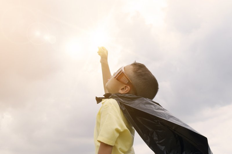 Photo of a child running around outside with a cape on